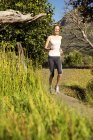 Smiling woman jogging in rural landscape — Stock Photo