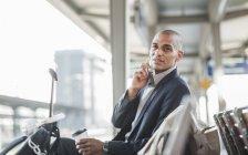 Geschäftsmann am Bahnhof telefoniert mit Smartphone — Stockfoto