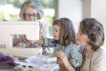 Mutter, Tochter und Großmutter, die Arbeit an der Nähmaschine — Stockfoto