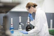 Feminina cientista trabalhando em laboratório com pipetas — Fotografia de Stock