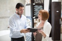 Bathroom shop salesman showing catalogue to female customer — Stock Photo
