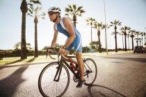Mature caucasian male triathlet training on bicycle — Stock Photo