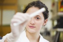 Young lab technician holding medical sample — Stock Photo