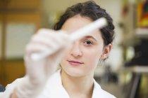 Jeune technicien de laboratoire tenant un échantillon médical — Photo de stock