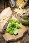 Pesto alla Genovese, basil leaves, parmesan, pine nuts, olive oil and raw trofie noodles on wooden table — Stock Photo
