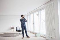 Giovane in piedi nel suo salotto guardando attraverso la finestra — Foto stock