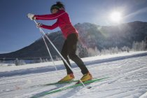 Side portrait of female skier in snow-covered landscape — Stock Photo