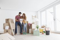 Young couple in new flat with cardboard boxes looking at ground plan — Stock Photo
