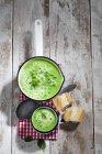 Кастрюля и кружка горохового супа, ложка, нарезанный багет и ткань на дереве — стоковое фото