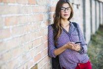 Брюнетка молодая женщина с очки Холдинг сотовый телефон — стоковое фото
