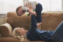 Мати підйому малюк син лежачи на дивані — стокове фото