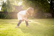 Little girl on a meadow using magnifying glass — Stock Photo