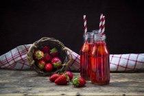Tre bottiglie di vetro di limonata di fragole fatta in casa e wickerbasket di fragole — Foto stock