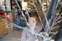Jeune femme travaillant dans un atelier de réparation de vélos — Photo de stock