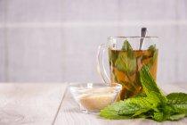 Té vaso de té de menta fresca y tazón de vidrio con azúcar de caña - foto de stock
