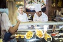 Männlichen Chef und Assistent hilft Kunden bei Lebensmittel-Anzeige — Stockfoto