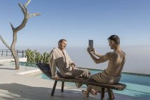 Two young men at the poolside taking a photograph with digital tablet — Stock Photo