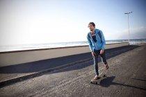 Mann mit Longboard auf Küstenstraße — Stockfoto