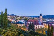 Alemania, Baden-Wuerttemberg, Baden-Baden, Paisaje urbano con iglesia colegiata por la noche - foto de stock