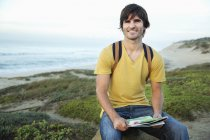 Smiling man with map at the coast — Stock Photo