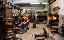 Senior blacksmith working in hammer mill — Stock Photo