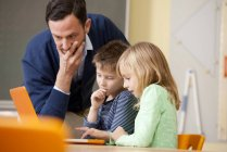 Teacher with pupils using laptop in classroom — Stock Photo