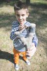 Portrait of boy holding slingshot outdoors — Stock Photo