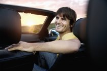Smiling man in convertible at the coast at sunrise — Stock Photo
