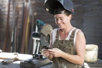 Schweißerin in Metallwerkstatt mit Handy — Stockfoto