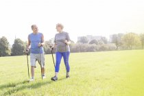 Senior couple doing Nordic Walking together in a park — Stock Photo
