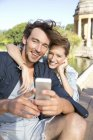 Счастливая молодая пара в парке делает селфи — стоковое фото