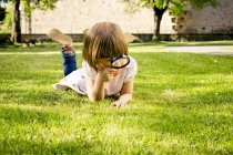 Little girl lying on a meadow using magnifying glass — Stock Photo