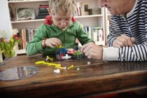 Grandfather and grandson assembling toy clock — Stock Photo