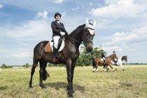 Портрет улыбаясь всадника на лошади на лугу — стоковое фото