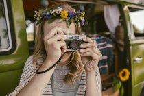 Cuadro de toma de mujer hippie con cámara analógica frente van - foto de stock