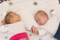 Neugeborene Zwillinge schlafen Hand in Hand im Bett — Stockfoto