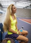 Young tennis player in an indoor tennis center having a rest — Stock Photo