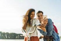 Lächelnde junge Paar mit dem Fahrrad und Handy — Stockfoto