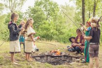 Germany, Saxony, Indians and cowboy party, Children rasting marshmallows on sticks — Stock Photo