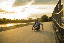 Человек, сидящий на скейте в вечерние сумерки. — стоковое фото