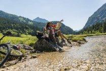 Áustria, Tirol, vale Tannheim, jovem casal com bicicletas de montanha e mapa sentado em brook — Fotografia de Stock