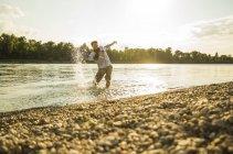 Homme debout au bord de l'eau éclaboussant avec de l'eau — Photo de stock