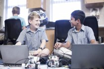 Schoolboys using laptops in robotics class — Stock Photo
