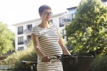 Portrait of smiling pregnant woman with bicycle — Stock Photo