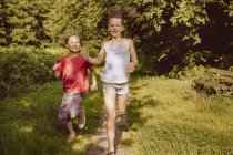Girl and boy running along path in nature — Stock Photo