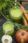 Смесь из морковного яблока в стекле и в банке со свежими ингредиентами — стоковое фото