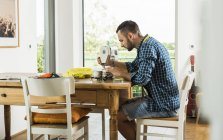 Young man at home using sewing machine — Stock Photo