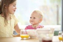Niña con hermana en la mesa del desayuno - foto de stock