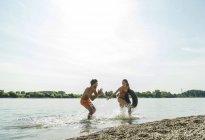 Игривый молодая пара с внутренней трубки в реке — стоковое фото