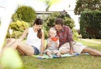 Батьки сидять з їх маленький син на ковдру в саду — стокове фото